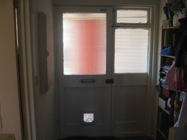 old single-glazed front entrance door from inside, with cat flap
